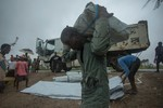 Man carrying supplies in aftermath of Cyclone Idai