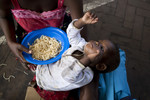Maria Andrey (1) eats food during a Red Cross distribution at a school